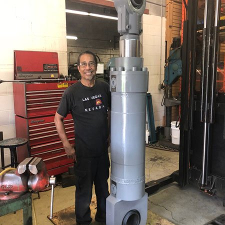 man standing after completion of Hydraulic cylinder repair